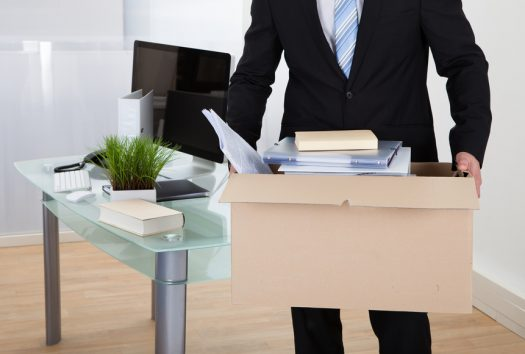 Businessman moving offices packing up all his personal belongings and files into a brown cardboard box